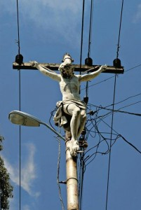 A statue of jesus crucified, mounted on a telephone pole.